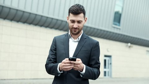 Successful Businessman Standing in the Foreground. Holding Mobile Device in his Hands. Looking on Smartphone's Screen. Young Man Wearing Official Clothes. Classical Jacket. Business Lifestyle.