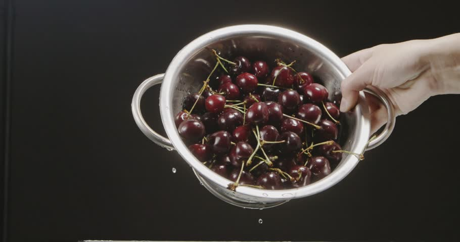 A large red cherry falls out of the metallic colander and drops of water scatter in different directions. A colander holds women hand on a black background. Slow motion. Full HD video, 240fps,1080p