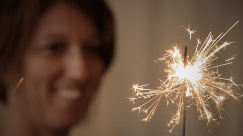 A happy woman celebrating something with a burning fuse spark.