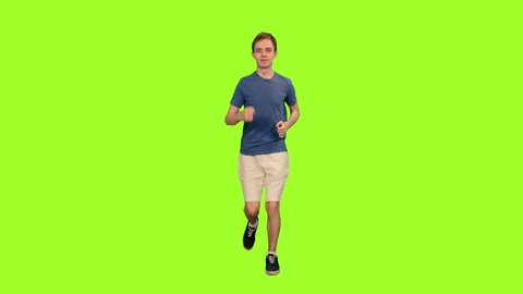 Handsome young man in shorts and blue t-shirt jogging on green chroma key background, Front view, 4k pre-keyed footage