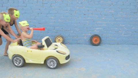 Funny kids in superhero's masks roll their little brother on yellow car. Boys are happy together and dream of adventures, travels, exploits.