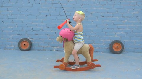 Funny boy blond in superhero mask is sitting on toy rocking horse. child is armed with sword and signal horn and dreams of adventures, travels, exploits. Concept training of spirit, patriotizm