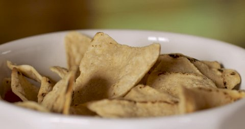 Two hands one from a man, one from a woman, grab the same tortilla corn chip from a bowl and play tug of war - close up