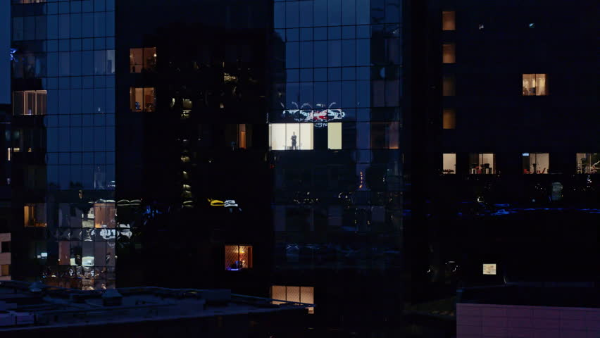 Aerial View Footage: From Outside into Office Building with Businessman Working and Looking out of the Window. Beautiful Flying Away Shot of The Financial Business District Skyscrapers in the Evening.