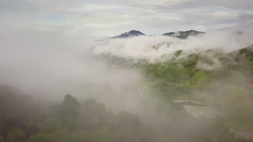 Aerial view of a village in the lush green rain cloud cover tropical rain forest mountain during the rainy season in the northern Thailand