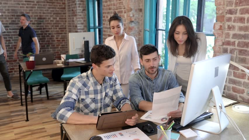 Start up of Creative Young Team Working at the Office. Productive Coworkers Standing at the Table. Successful Team Leader Holding Folder with Graphs. Casual Dressed Collegues Having Meeting. | Shutterstock HD Video #1014677732