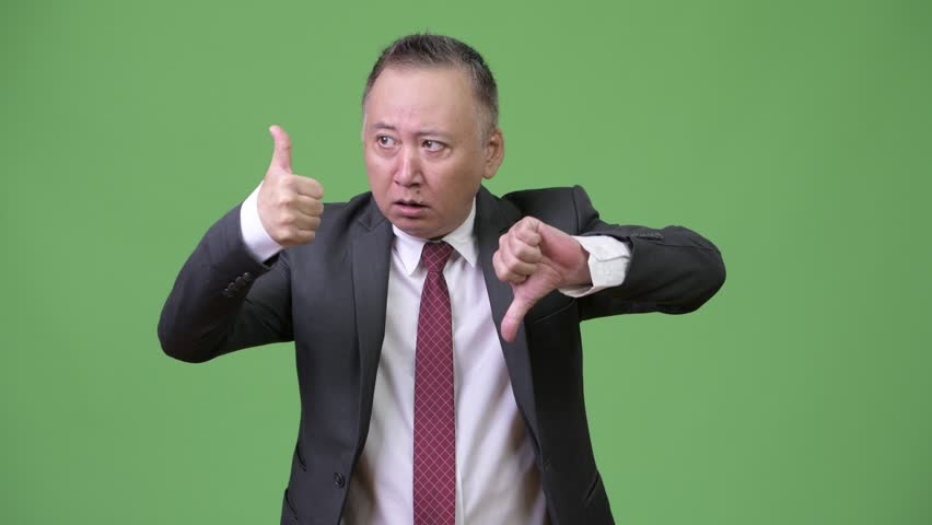 Mature confused Japanese businessman choosing between thumbs up or thumbs  down