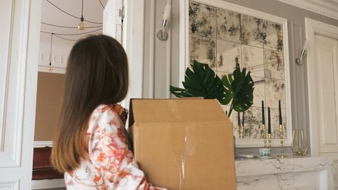 Young beautiful woman walk in to a new appartment with cardboard box. Moving to a new appartment