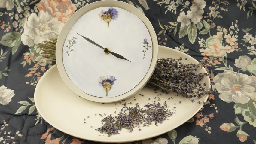 A clock, a white faience dish, and bouquet of dried lavender against the background of fabric with a floral pattern, floristic composition
