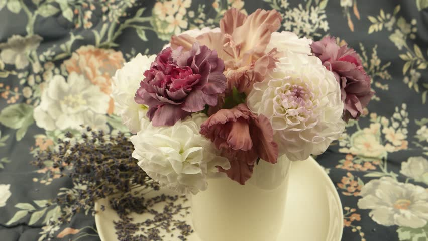 White dahlias, pale pink carnations in a vase  and a bouquet of dry lavender against of  fabric with a floral pattern, a floral arrangement
