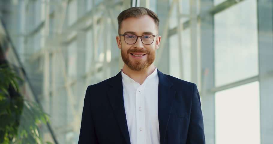 Good looking young Caucasian businessman in glasses and official style turning his head to the camera and smiling. Portrait. | Shutterstock HD Video #1014757922
