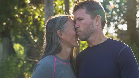 Handheld shot of affectionate couple talking while standing against trees