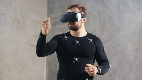 Young athletic man with beard wears motion capture suit with sensors and vr  glasses headset moving in virtual reality taking something and looking at  his hands excited experience cyber space online