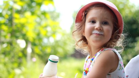 Child girl drinks a milk drink from a bottle or kefir, smiles and shows a white mustache from yogurt.