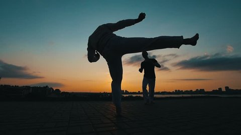 Silhouettes of two sports men who train skills of martial art of capoeira against the background of the amazing sky