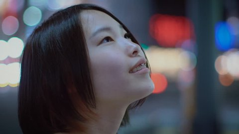 Portrait of the Attractive Japanese Girl with Piercing and Wearing Casual Looks around Her in Wonder. In the Background Big City Advertising Billboards Lights Glow in the Night.