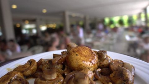 Point of view. Buffet Restaurant. Waiter or person put fried mushrooms in a plate and walks around the restaurant. Eating and food concept.