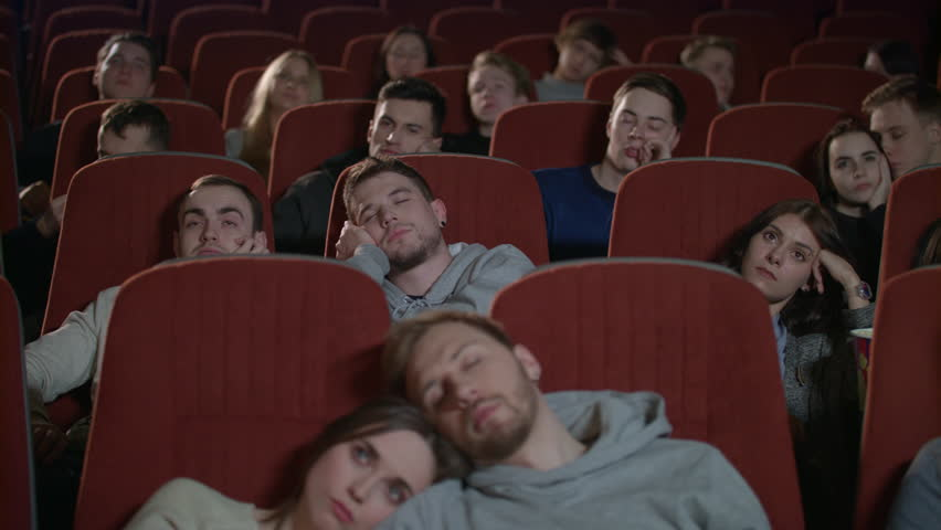 People watch boring movie at cinema in slow motion. Group of young people sleeping watching boring movie in cinema. Bored audience watching film in cinema. Spectators fall asleep from boring film