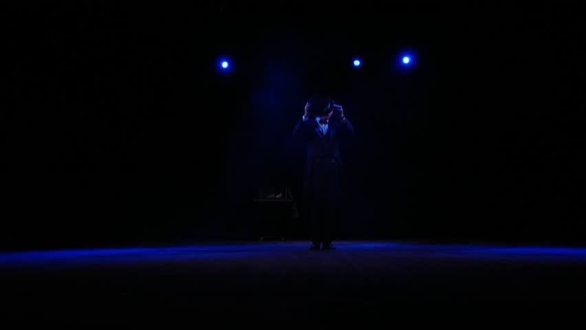 The magician on stage appears out of the darkness. | Shutterstock HD Video #1014830272
