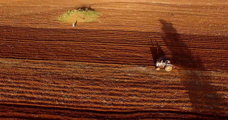 Aerial clip of a tractoring on a red field in the Karatu area, Tanzania.