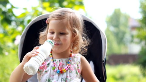 Child girl sits in a stroller and drinks a milk drink from a bottle or kefir.