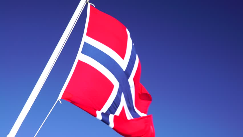The National flag of Norway blowing in the wind, Clear Blue Sky And Sea in Background, Travel in Norway