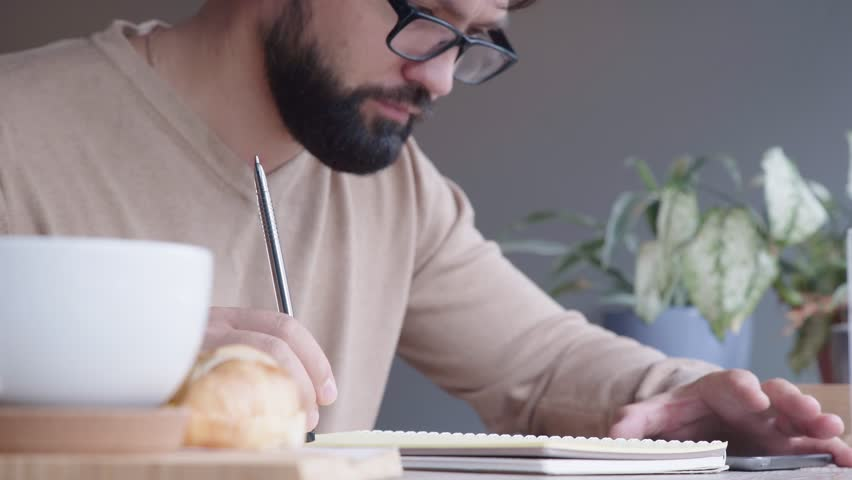 A young man with a beard, wearing glasses, a light pullover, sits in a cafe, drinks his morning coffee and writes plans in a notebook. Concept of morning coffee, planning, scheduling, to-do list.