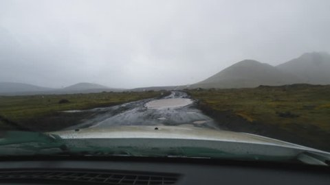 View from a car driving on a muddy road with potholes in Iceland.