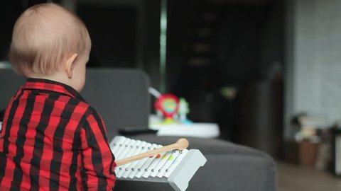 Baby boy play xylophone at home, slow motion