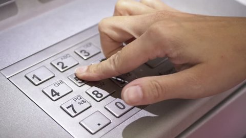 ATM Banking Hand Enter Pin Code In Cash Machine. Female hand typing personal pin code in a ATM cash machine. close up shot