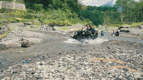 Two woman and man driving jeep in river