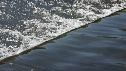 Water flowing cleanly over a weir.