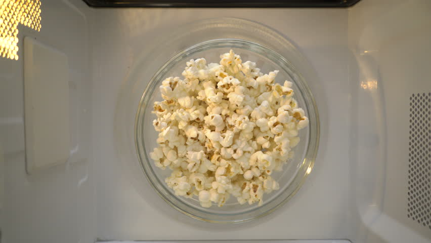 Making popcorn in the microwave. Bowl of popcorn turning around in microwave top view.