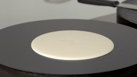 Cook prepares pancakes on the professional surface of the plate in slow motion