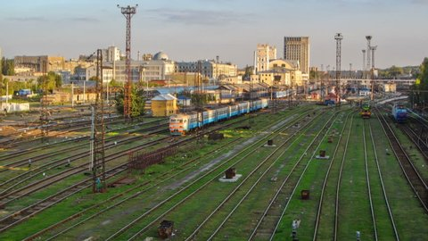 The building of the Southern Railway Station and the trains on platforms against timelapse Kharkiv, Ukraine. Aerial view from a bridge.