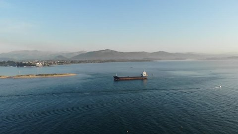 Santander, Cantabria, Spain. Bay of Santander, a huge cargo ship, beach, water, boats, sky, ships, mountains in the background, aerial view. Spain by drone 4k.