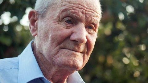 Very old man portrait with emotions. Grandfather is smiling and looking to camera. Portrait: aged, elderly, senior. Close-up of old man sitting alone outdoors. Slow motion. 4k