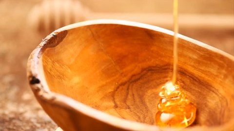 Honey pouring honey in wooden bowl.  Close-up. Healthy organic Thick honey dipping from the honey spoon, closeup. 4K UHD video footage. Slow motion