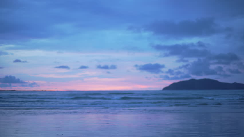 Out of focus background plate of beautiful purple and blue sunset on the beach in Costa Rica for compositing or keying. Blurred or defocused shot of ocean sun set for green screen composite. 4k