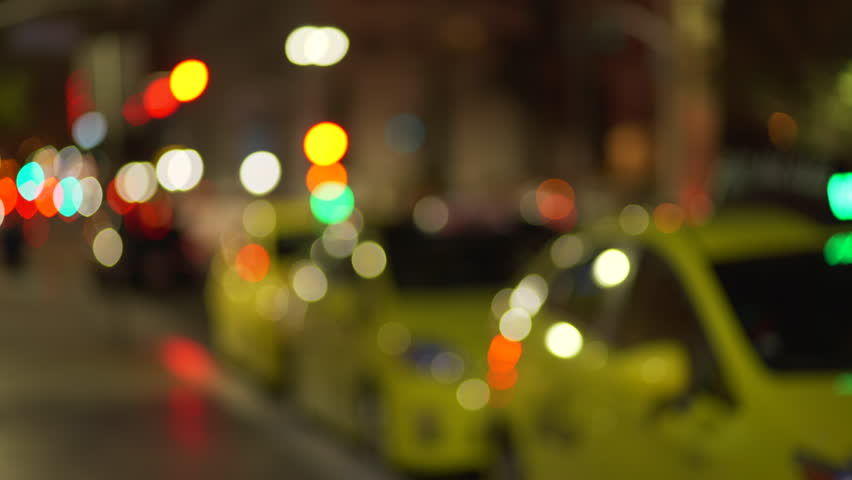 Out of focus background plate of taxi cab line parked on city street downtown at night. Blurry Video backdrop of urban area with bokeh lights for green screen compositing. 4k