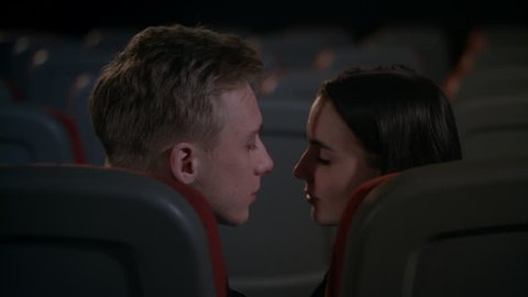 Love couple passion in cinema after film. Boyfriend and girlfriend kissing in back seats at cinema after session. Romantic kiss at cinema date in slow motion. Kissing couple in empty movie theater