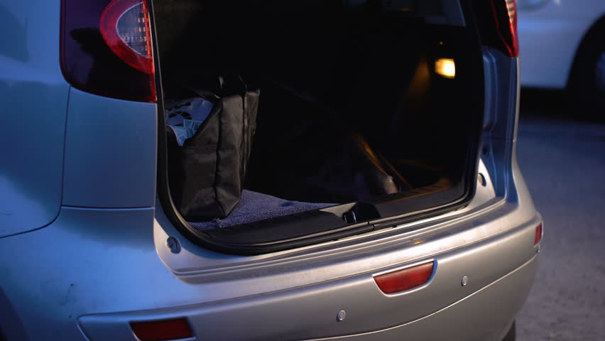 Thief throwing bag with money in car trunk and driving away, bank robbery
