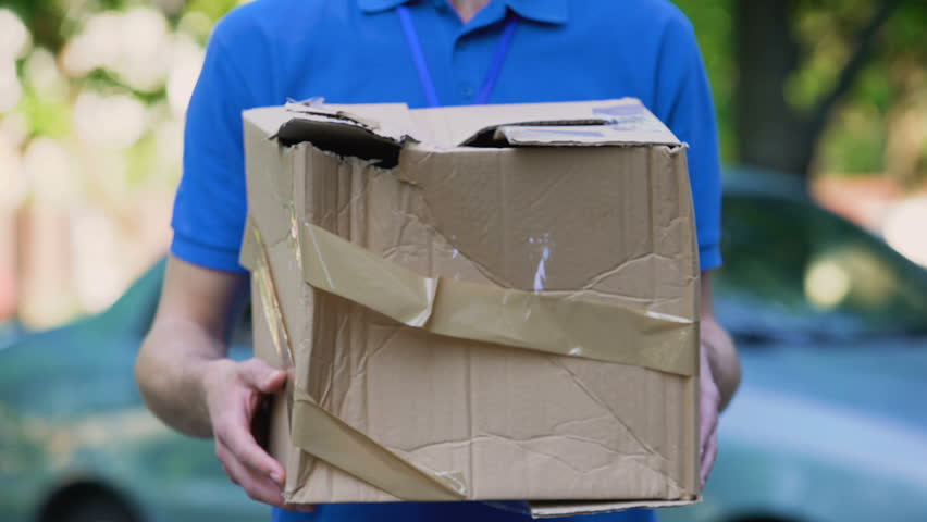 Male courier showing damaged box, cheap parcel delivery, poor shipment quality | Shutterstock HD Video #1015043242