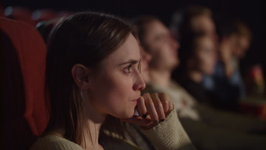 Concentrated girl watching thrilling movie at cinema. Young woman watching movie in movie theater. Pretty girl watching exciting movie in cinema. Enjoy cinema concept | Shutterstock HD Video #1015060102