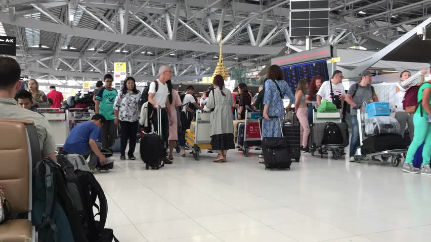 SUVARNABHUMI AIRPORT, THAILAND - MARCH 25, 2018 : Many people of passengers walking in the terminal at Suvarnabhumi of international airport in Thailand. (Effects time lapse)