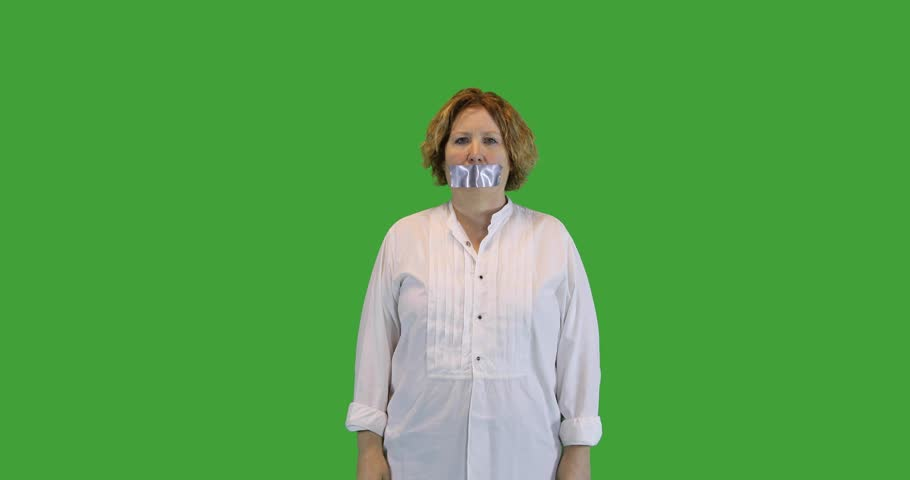 Mature woman removing duct tape on mouth as metaphor for taking away censorship on green screen.