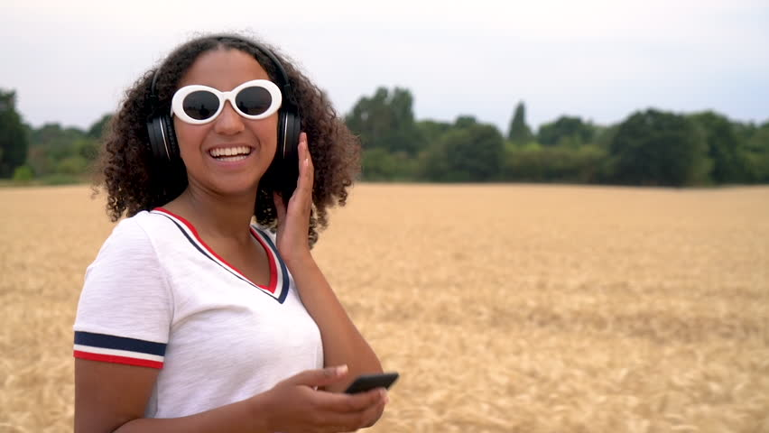 Slow motion tracking video of beautiful mixed race African American girl teenager young woman wearing a white t-shirt and sunglasses listening to music on her cell phone and wireless headphones