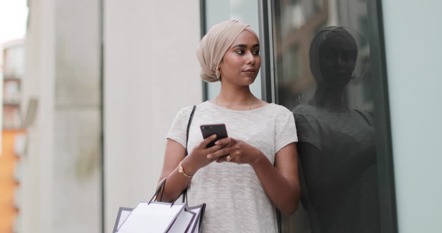 Muslim woman using a smartphone on a shopping trip