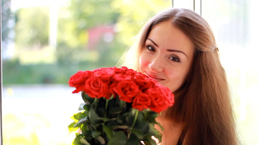 Young woman with a bouquet of red roses near an open window. A beautiful girl enjoys the aroma of flowers #1015132582