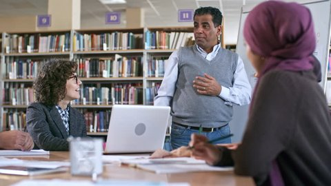 Mid-aged arab man standing at flipchart and explaining English grammar to group of migrant students